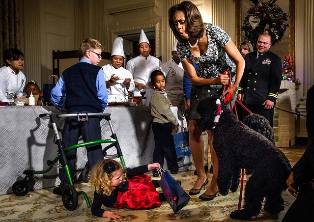 Honorable Mention, General News. Photo by Kevin Dietsch: First Lady Michelle Obama attempts to restrain the family dog Sunny after he startled Ashtyn Gardner, 2, of Mobile, Alabama, causing her to fall during a holiday craft event, in the State Dining Room at the White House. (Photo by Kevin Dietsch)