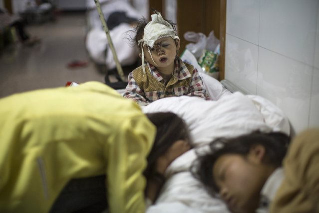 An injured child wakes up from sleep at a hospital in Ludian county, Zhaotong, Yunnan province, August 5, 2014. An earthquake in China on the weekend triggered landslides that have blocked rivers and created rapidly growing bodies of water that could unleash more destruction on survivors of the disaster that killed 410 people, state media reported on Thursday. (Photo by Reuters/Stringer)