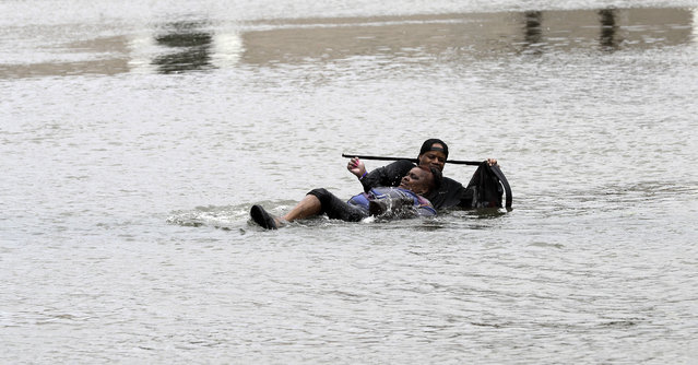 A man helps a woman in floodwaters from Tropical Storm Harvey Sunday, August 27, 2017, in Houston, Texas. (Photo by David J. Phillip/AP Photo)