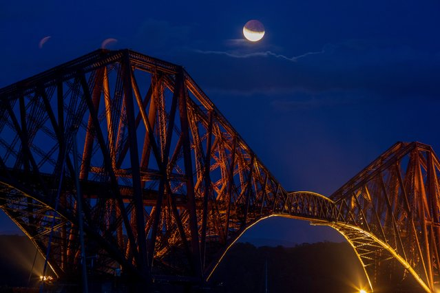 The moon rising above the Forth Rail Bridge in The Firth of Forth from North Queensferry, England on July 16, 2019. (Photo by South West News Service)
