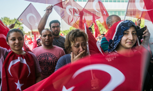 People wave Turkish flags and react after a military position was taken over at the Ataturk airport in Istanbul on July 16, 2016. (Photo by Gurcan Ozturk/AFP Photo)