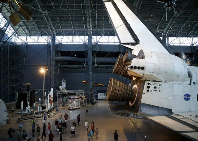 Tourists are dwarfed by the space shuttle orbiter Discovery on display at the Udvar-Hazy Smithsonian National Air and Space Annex Museum in Chantilly, Virginia August 28, 2015. (Photo by Gary Cameron/Reuters)
