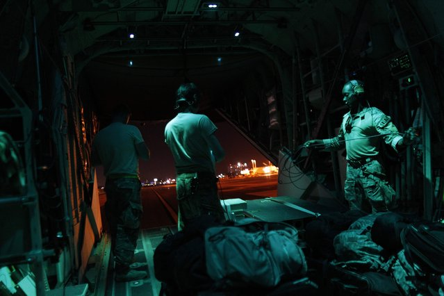 US Airforce crew members stand on the back of a C-130 cargo plane while taxiing at the Luis Munoz Marin Puerto Rico International Airport after delivering supplies to the Caribbean island which sustained extensive damage after the passing of Hurricane Irma in San Juan, on September 15, 2017. (Photo by Ricardo Arduengo/AFP Photo)