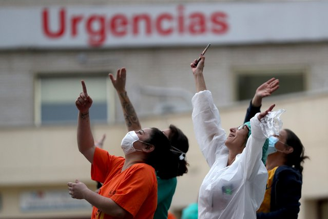 Medical staff react as they heard a helicopter flying over, while people applaud in support for healthcare workers, amid the coronavirus disease (COVID-19) outbreak, in Madrid, Spain, April 6, 2020. (Photo by Susana Vera/Reuters)