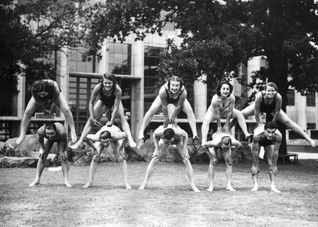 """Women divers who are competing in the European Championships at Wembley, London playing leapfrog with the speedway riders as part of a """"keep fit"""" regime. 6th July 1938. (Photo by George W. Hales)"""