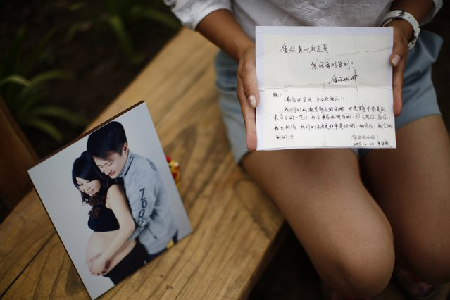 Cheng Liping, whose husband Ju was onboard Malaysia Airlines Flight MH370 which disappeared on March 8, 2014, shows a picture of she and her husband together and an old card with a message given by her husband, at a park near her house where she and her husband used to visit during an interview with Reuters in Beijing July 24, 2014. (Photo by Kim Kyung-Hoon/Reuters)