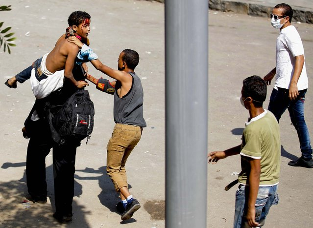 Egyptian protesters evacuate an injured youth toward a waiting ambulance during clashes with security forces near the U.S. Embassy in Cairo, Egypt, on September 14, 2012. (Photo by Nasser Nasser/Associated Press)