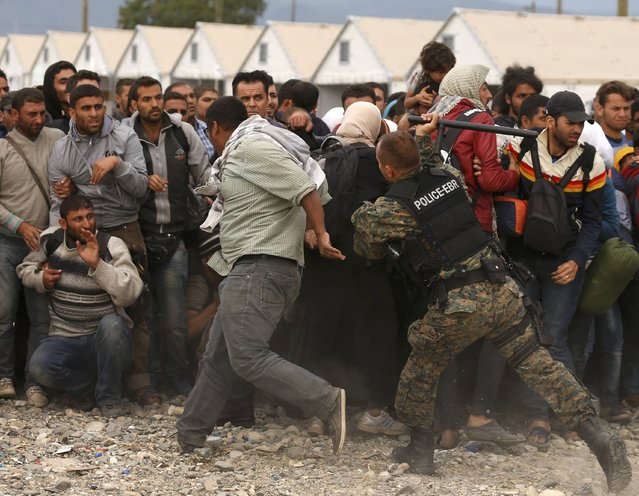 A policer officer hits a man with a baton as he tries to maintain order while migrants wait for trains at a temporary camp near Gevgelija, Macedonia, September 7, 2015.  Several thousand migrants in Macedonia boarded trains on Sunday to travel north after spending a night in a provisional camp. (Photo by Stoyan Nenov/Reuters)