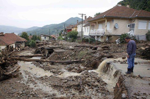 A man inspects the damage produced by heavy floods in Tekija village September 17, 2014. (Photo by Djordje Kojadinovic/Reuters)