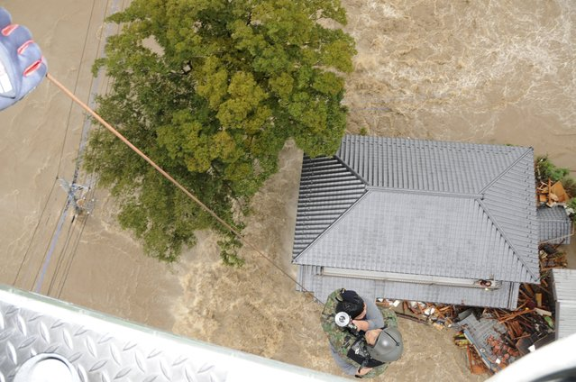 A resident is rescued by a member (bottom) of the Japan Self-Defense Force (JSDF) as they are lifted by a helicopter over a residential area flooded by the Kinugawa river, caused by typhoon Etau in Joso, Ibaraki prefecture, Japan, September 10, 2015, in this handout photograph taken and released byJoint Staff of the Defence Ministry of Japan. (Photo by Reuters/Joint Staff of the Defence Ministry of Japan)