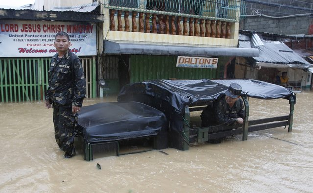 Soldiers wait for a tow truck with their stalled military rescue vehicle along a flooded road as tropical storm Fung-Wong battered the Philippine capital Manila September 19, 2014. Heavy rain in the Philippine capital, Manila, caused flooding in many areas on Friday, shutting schools, government offices and financial markets as a tropical storm made landfall to the north. Thousands of residents in low-lying areas were moved to higher ground, officials said, as flood waters rose quickly after the equivalent of half a month's usual rain fell in six hours. (Photo by Erik De Castro/Reuters)
