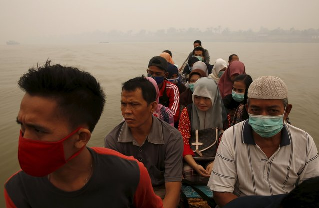Workers use their mask as sit on a wooded boat during across the river as the haze shrouded Batanghari River in Jambi, Indonesia Sumatra island, September 15, 2015. (Photo by Reuters/Beawiharta)