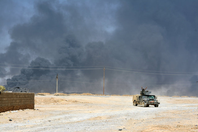 Smoke rises from clashes with Islamic State militants on the outskirt of Al Qayyarah, Iraq, August 14, 2016. Picture taken August 14, 2016. (Photo by Reuters/Stringer)