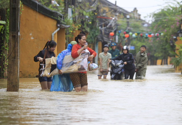 People move furniture in a flooded street in Hoi An, Vietnam, Monday, November 6, 2017. (Photo by Hau Dinh/AP Photo)