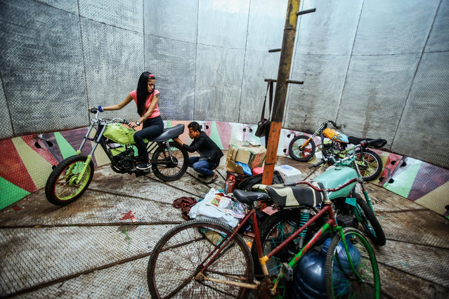 """A picture made available on 16 August 2016 shows a young dare devil motorbike rider, Karmila Purba (L), 18, and her mentor Tora Palevi checking her motorbike before the show time of """"Tong Setan"""" or Davil's Barrel show, at a traditional night carnival in Deliserdang, North Sumatra, Indonesia, 11 August 2016. (Photo by Dedi Sinuhaji/EPA)"""