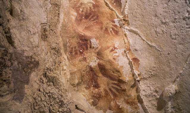 This handout picture released by the journal Nature, on October 8, 2014, shows hand stencils marking a cave wall in Maros karsts on the Indonesian island of Sulawesi. The silhouette of hands on a cave wall is 40,000 years old, showing that Europe was not the birthplace of art as long believed, researchers said. (Photo by Kinez Riza/AFP Photo/Nature)