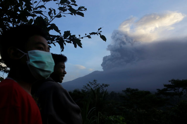 Villagers watch as Mount Agung volcano spews ash during an eruption from the Volcanic Observatory in Rendang Village, Karangasem, Bali, Indonesia November 26, 2017. (Photo by Johannes P. Christo/Reuters)