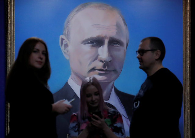 """People stand in front of a painting depicting Russian president Vladimir Putin at the """"SUPERPUTIN"""" exhibition at UMAM museum in Moscow, Russia on December 6, 2017. (Photo by Maxim Shemetov/Reuters)"""