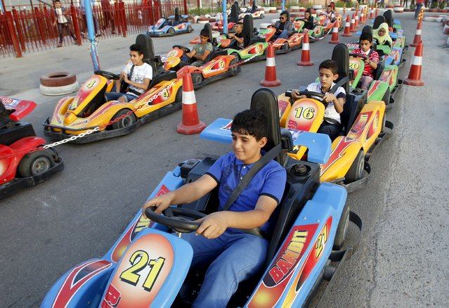 Children take a ride at an amusement park on the first day of the Muslim festival of Eid al-Adha in Baghdad September 24, 2015. (Photo by Khalid al-Mousily/Reuters)