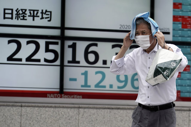 A man walks in the rain past an electronic stock board showing Japan's Nikkei 225 index at a securities firm in Tokyo Friday, July 10, 2020. Asian stock markets followed Wall Street lower Friday on worries economic improvements might fade as coronavirus cases increase in the United States and some other countries. (Photo by Eugene Hoshiko/AP Photo)