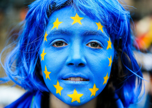 """An actor has her face painted in the colors of the European Union flag as she joins a joint protest action titled """"EU At the Energy Crossroads"""" of """"Climate Action Network Europe"""", """"Friends of the Earth Europe"""", """"Greenpeace"""" and """"World Wildlife Fund"""" (WWF) to highlight the decision on Clean Energy laws facing European governments, on the sidelines of an EU Transport, Telecommunications and Energy (TTE) ministers council meeting, in front of the European Council in Brussels, Belgium, 18 December 2017. EU Energy Ministers are expected to finalize their position on the """"Clean Energy Package"""" of legislative proposals that will guide energy policy all across Europe for the next decade. (Photo by  Stephanie Lecocq/EPA/EFE)"""