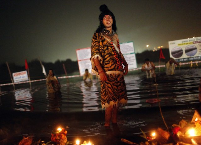 A man dressed as as Hindu Lord Shiva stands in the waters of the Yamuna river after arriving to worship the Sun god Surya during the Hindu religious festival of Chatt Puja in New Delhi October 30, 2014. (Photo by Anindito Mukherjee/Reuters)