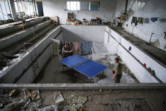 In this photo taken on Thursday, August 25, 2016, Ukrainian soldiers play table tennis at a damaged swimming pool in the village of Marinka, near Donetsk, eastern Ukraine. More than 9,500 people have been killed in the fighting that began in April 2014, according to United Nations figures, but despite the carnage or the weariness of those inflicting it, there's little expectation it will actually stop anytime soon. (Photo by Max Black/AP Photo)