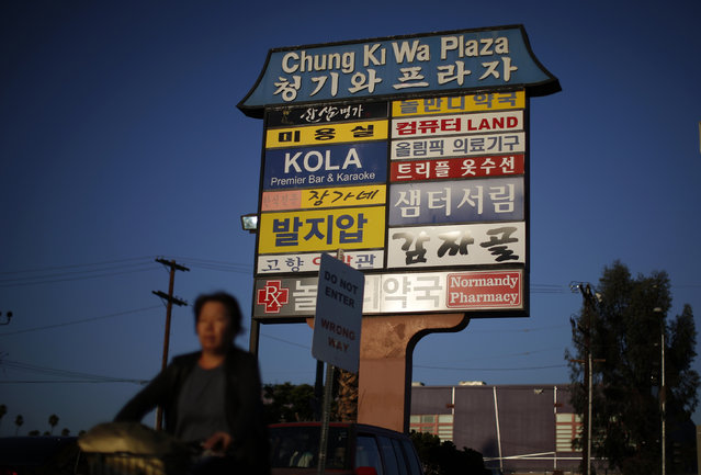 A woman cycles past a mall sign in Korean in the Koreatown area of Los Angeles, California August 12, 2014. (Photo by Lucy Nicholson/Reuters)