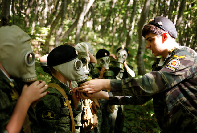 Fifth-grade students of the General Yermolov Cadet School, instructed by a tenth-grader, take on gas masks during their first military tactical exercise on the ground, which includes radiation resistance classes, forest survival studies and other activities, in Stavropol, Russia, September 10, 2016. Picture taken September 10, 2016. (Photo by Eduard Korniyenko/Reuters)