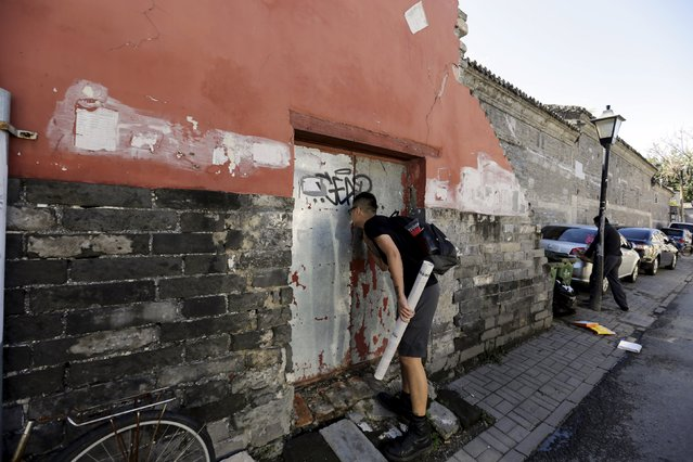 """Chinese artist ROBBBB checks a closed door before he pastes his work in a traditional alleyway, or """"hutong"""", in central Beijing September 25, 2015. (Photo by Jason Lee/Reuters)"""