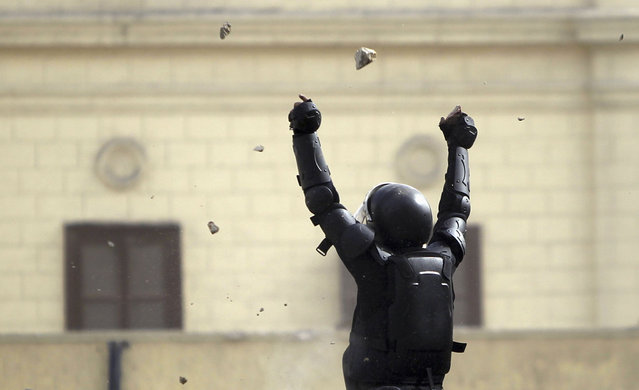 A riot police officer gestures a during clashes with protesters throwing stones at him along Sheikh Rihan street near Tahrir Square, on January 25, 2013. (Photo by Amr Abdallah Dalsh/Reuters/The Atlantic)