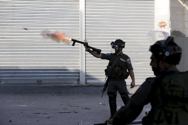 An Israeli border policeman fires tear gas towards Palestinian protesters during clashes at a checkpoint between Shuafat refugee camp and Jerusalem October 9, 2015. (Photo by Ammar Awad/Reuters)
