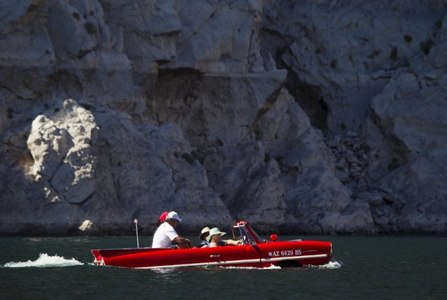 A 1963 Amphicar, driven by Rob Vondracek of Fountain Hills, Arizona, heads back to the marina after a trip to Hoover Dam during the first Las Vegas Amphicar Swim-in near Las Vegas, Nevada October 9, 2015. (Photo by Steve Marcus/Reuters)