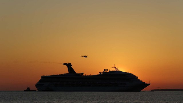The sun sets as the Carnival Triumph is towed into Mobile Bay near Dauphin Island, February 14, 2013. (Photo by Dave Martin/Associated Press)