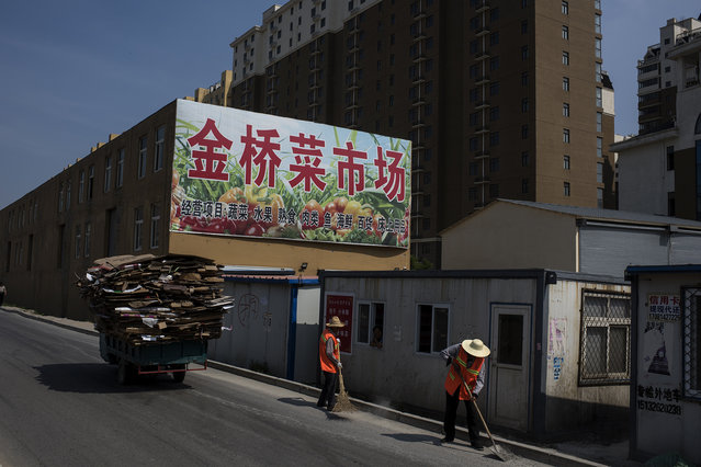 Workers sweep up a road leading to a new development in Yanjiao on May 21, 2016. Yanjiao is a satellite city of Beijing, with 700,000 people, that is rapidly consuming all of the villages surrounding it. Beijing is a prime example of China's rapid urbanization and move towards creating supercities with populations over 100 million people. (Photo by Michael Robinson Chavez/The Washington Post)
