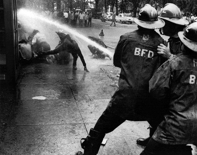 Firefighters turn their hoses full force on civil rights demonstrators in Birmingham, Alabama, on July 15, 1963. (Photo by Bill Hudson/AP Photo)
