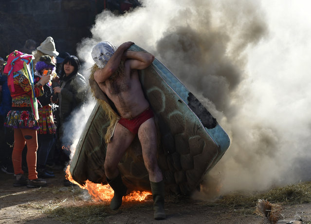 A masked participant carries a burning matress during the ancient carnival of Zubieta, in the northern Spanish Navarra province on January 30, 2018. The yearly three day festivities, revolving mainly around agriculture and principally sheep hearding, run on the last Sunday, Monday and Tuesday of January where Navarra Valley locals from two villages dress up and participate in a variety of activites as they perform a pilgrimage through each village. (Photo by Ander Gillenea/AFP Photo)