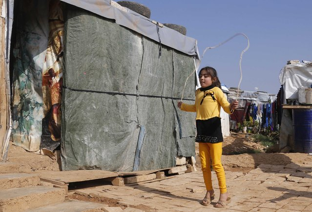 A Syrian refugee girl plays outside a tent at a refugee camp in Zahle in the Bekaa valley November 18, 2014. In October, Lebanon, which has the highest per capita concentration of refugees in the world at one in four residents, said it could not cope with more than one million Syrians and has asked for funds to help look after them. (Photo by Mohamed Azakir/Reuters)