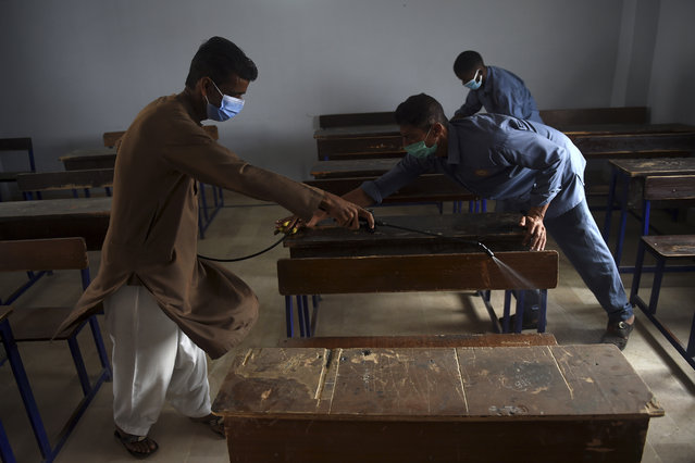 A worker sprays disinfectant in a classroom at a private school in Karachi on September 14, 2020 following the government's announcement to reopen educational institutes starting from September 15, nearly six months after the spread of the Covid-19 Coronavirus. (Photo by Rizwan Tabassum/AFP Photo)