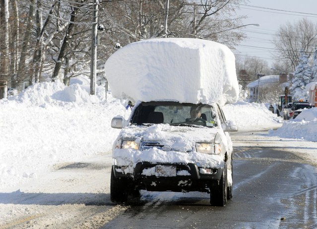 A vehicle, with a large chunk of snow on it's top, drives along Route 20 after digging out after a massive snow fall in Lancaster, N.Y. Wednesday, November 19, 2014. Another two to three feet of snow is expected in the area. (Photo by Gary Wiepert/AP Photo)