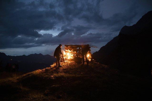 2 men light a bonfire on Saturday, August 1st, 2020 on the Engstligenalp above Adelboden. On the Swiss national holiday, bonfires were lit on several mountain peaks around Adelboden. (Photo by Peter Klaunzer/Keystone)