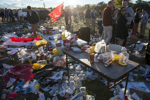 Revellers stand amid the garbage created during a tailgate party at the Far Hills Race Day at Moorland Farms in Far Hills, New Jersey, October 17, 2015. (Photo by Stephanie Keith/Reuters)