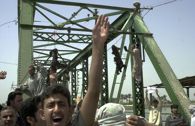 In this March 31, 2004 photo, Iraqis chant anti-American slogans as charred bodies hang from a bridge over the Euphrates River in Fallujah, west of Baghdad. A convoy containing four American contractors from the private military company Blackwater USA had been ambushed, all four inside were killed. (Photo by Khalid Mohammed/AP Photo/The Atlantic)