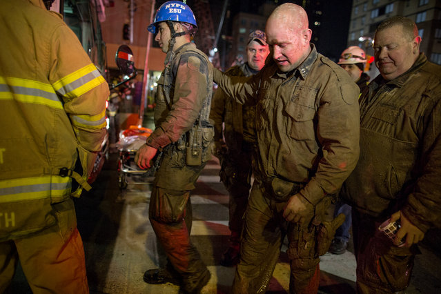 Officers of the New York City police Emergency Services Unit, covered in mud and dirt, walk to a waiting bus to warm up after securing the rescue of a construction worker trapped underground at an MTA subway construction project in New York early Wednesday, March 20, 2013. The worker, trapped for several hours, was lifted from underground with the assistance of the New York police and fire departments. Fire officials say he is awake and conscious and is being evaluated at a local hospital. (Photo by Craig Ruttle/AP Photo)