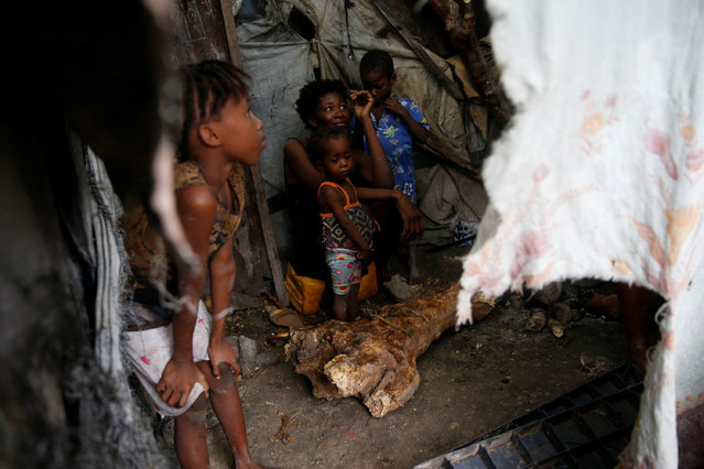Members of a family warm themselves next to a fire while Hurricane Matthew approaches Port-au-Prince, Haiti, October 3, 2016. (Photo by Carlos Garcia Rawlins/Reuters)