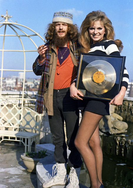 Norwegian actress Julie Ege holds the Golden Album on behalf of Warner Reprise, to give to the Jethro Tull pop group, is seen with Ian Anderson a member of the group, in London, February 19, 1971. The group had sold one million dollars of sales of the groups latest album, Benefit. (Photo by Robert Dear/AP Photo)