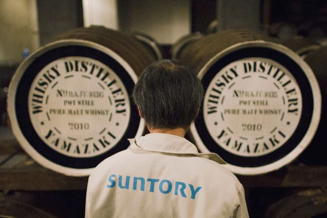 A worker stands in front of whisky casks at Suntory Holdings' Yamazaki Distillery in Shimamoto town, Osaka prefecture, near Kyoto,  December 1, 2014. (Photo by Thomas Peter/Reuters)