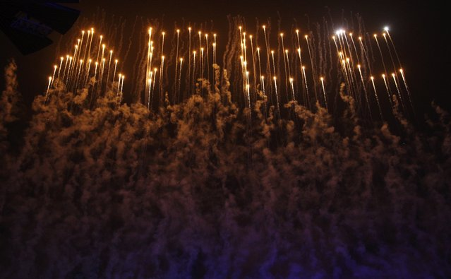 """Fireworks explode to form the letters """"APEC"""" above the National Stadium, also known as the """"Bird's Nest"""", during a lights and fireworks show to celebrate the Asia-Pacific Economic Cooperation (APEC) Leaders' Meeting, in Beijing November 10, 2014. (Photo by Reuters/China Daily)"""