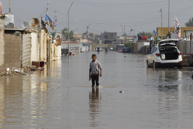 A boy stands at  a flooded street after heavy rainfall in Baghdad,Iraq October 31 2015. (Photo by Ahmed Saad/Reuters)