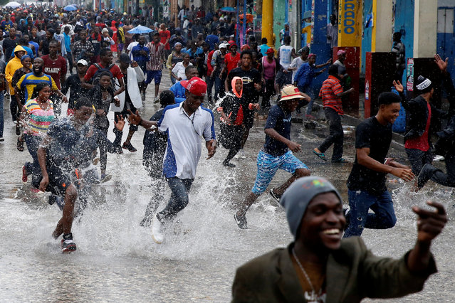 Supporters of Fanmi Lavalas political party splash around in water on a flooded street as they take part in a gathering while Hurricane Matthew passes in Port-au-Prince, Haiti, October 4, 2016. (Photo by Carlos Garcia Rawlins/Reuters)